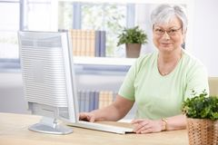 Mature lady with computer smiling stock photography