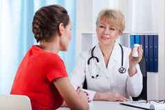 Mature Lady doctor showing patient medication Stock Images