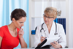 Mature Lady doctor shows a patient test results Stock Photography