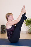 Mature lady doing yoga. Mature lady in fit condition doing yoga and showing great flexibility stock photo
