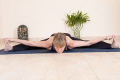 Mature lady doing yoga. Mature lady in fit condition doing yoga and showing great flexibility stock image