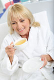 Mature lady drinking beverage after bathing Royalty Free Stock Images