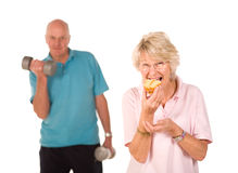 Mature lady eating cake at the gym Royalty Free Stock Images