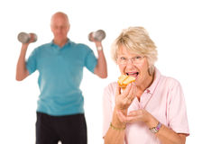 Mature lady eating cake at the gym Royalty Free Stock Image