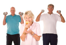 Mature lady eating cake at the gym Stock Image