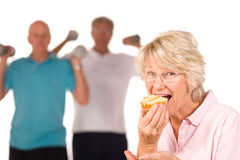 Mature lady eating cake at the gym Royalty Free Stock Photography