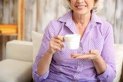 Mature lady enjoying hot drink Royalty Free Stock Photos