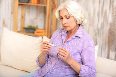Mature lady has problems with health. Sick old woman is measuring her temperature. She is sitting on couch and looking at thermometer with sadness Royalty Free Stock Photo