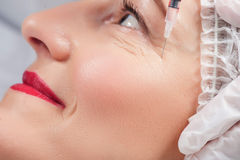 Mature lady is having facial treatment by beautician Royalty Free Stock Images