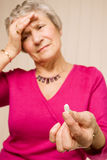 Mature lady with headache holding tablet or pill Stock Photo