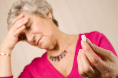 Mature lady with headache holding tablet or pill. Mature older lady holding a pain relief tablet or pill, while holding her head with her hand in discomfort Stock Image