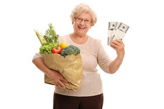 Mature lady holding groceries and money Royalty Free Stock Image