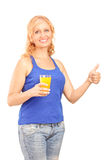 Mature lady holding a juice and giving thumb up Royalty Free Stock Photo