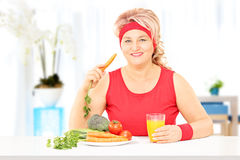 Mature lady at home eating a healthy meal Stock Images