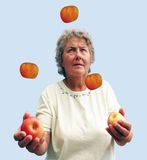 Mature Lady Juggling her diet. Juggler on a Balanced Diet Royalty Free Stock Photos
