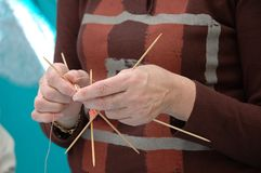 Mature lady knitting. Hands of a mature lady knittinng an orange scarf Royalty Free Stock Photography