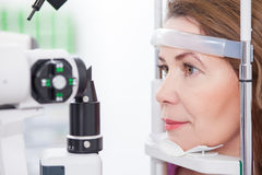 Mature lady is looking into eye test machine Stock Photos