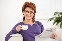 Mature lady with newspaper while drinking coffee stock images