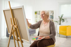Mature lady painting on a canvas. With a paintbrush at home stock photography