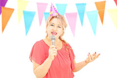 Mature lady with party hat singing on microphone at a birthday p Stock Photo