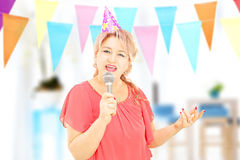 Mature lady with party hat singing on microphone at party Stock Images