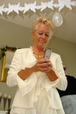Mature lady on a party sending SMS stock photo