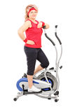 Mature lady posing on a cross trainer machine Royalty Free Stock Images