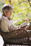 Mature lady reading and relaxing  outdoors Stock Photos