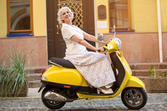 Mature lady rides a scooter. Side view of yellow scooter. Traveller rides with comfort. Trip won't take much time Royalty Free Stock Image