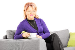 Mature lady seated on a sofa holding a cup of coffee Stock Photography