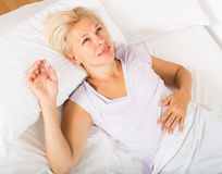 Mature lady in shirt awaking on bed Royalty Free Stock Photography