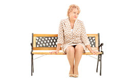 Mature lady sitting on a bench isolated on white background Stock Photography