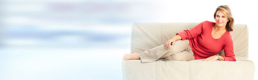 Mature lady sitting sofa Stock Images