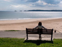 Mature lady sitting down looking out over Swansea bay Royalty Free Stock Photos