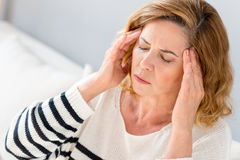 Mature lady suffers from headache. What terrible pain. Senior woman feels ache in head. She is sitting and touching temples with sorrow royalty free stock image