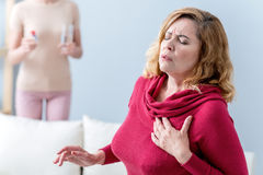 Mature lady suffers from heartache. Senior women feels terrible pain in heart. She is touching her chest with frustration. Her daughter is standing with pills Royalty Free Stock Photography