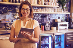 Mature lady with a toothy smile. Mature lady working in coffee shop looking at her tablet with a toothy smile with workflow area out of focus behind her Stock Image