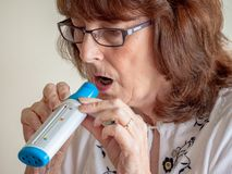Mature lady using lung air flow monitor royalty free stock photography