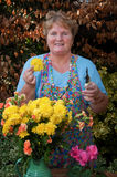 Mature lady working flowers outside portrait Royalty Free Stock Photo