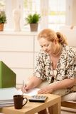 Mature lady working at home Royalty Free Stock Photos