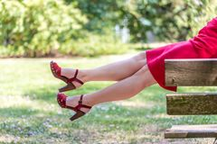 Mature legs swinging. Mature woman sitting on a table in a garden and dangling legs royalty free stock photos