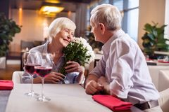 Merry mature couple demonstrating love. Mature love. Lovely sincere mature women grinning while holding flowers while men staring at her Royalty Free Stock Photo
