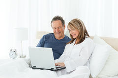 Mature lovers looking at their laptop Royalty Free Stock Photos