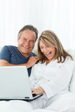 Mature lovers looking at their laptop Royalty Free Stock Photo