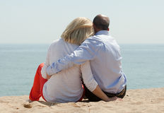 Mature lovers sitting on beach Stock Images