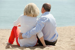 Mature lovers sitting on beach Royalty Free Stock Image