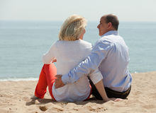 Mature lovers sitting on beach Royalty Free Stock Photography