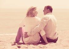 Mature lovers sitting on beach Stock Photo