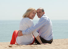 Mature lovers sitting on beach Royalty Free Stock Images