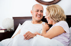 Mature loving couple lounging in bed after awaking cuddling Royalty Free Stock Image